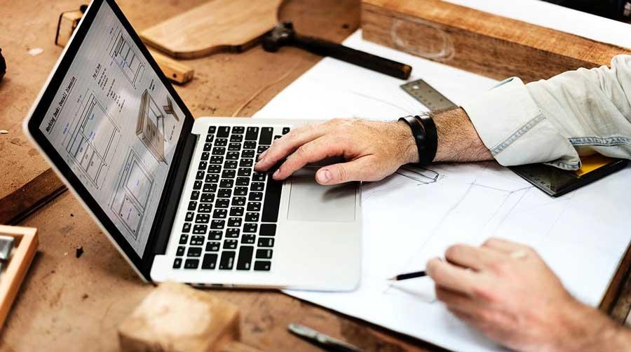 Fa, tervező asztalon egy tervlapra helyezett laptop, amit valaki használ éppen.