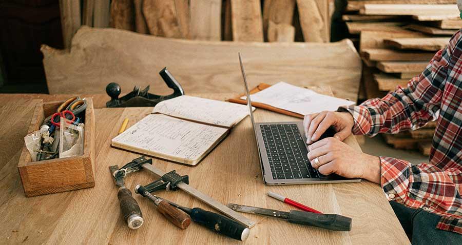 Fa asztal, a háttérben fa deszkákkal. Az asztalon különböző szerszámok, és egy laptop, ami előtt ül valaki.