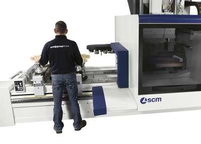 A képen az scm gyári technikusa látható ahogy a munka darabot elszedi a gépről.