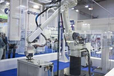 A képen az scm festő robotja látható egy bemutató teremben plexivel körbe zárva munka közben.